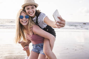 Two girlfriends having fun on the beach, carrying each other piggyback, taking smartphone selfies - UUF19045