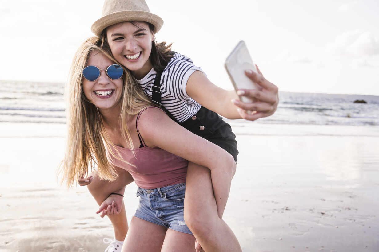 Two girlfriends having fun on the beach, carrying each other piggyback, taking smartphone selfies - UUF19045 - Uwe Umstätter/Westend61