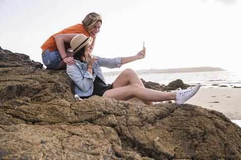 Two girlfriends sitting on rocky beach, taking smartphone selfies - UUF19048