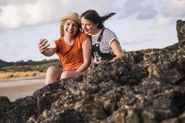 Two girlfriends sitting on rocky beach, taking smartphone selfies - UUF19054