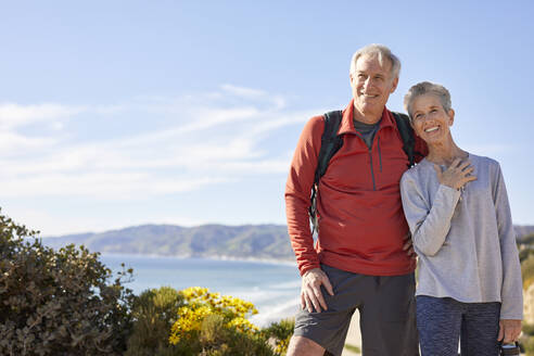 Cheerful senior couple standing against sky during sunny day - CAVF64942