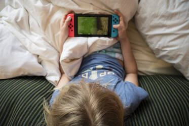 Child Lounging in Bed Playing Hanheld Video Game - CAVF65044
