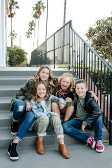 Smiling siblings with fun shoes on steps with iron railing - CAVF65110
