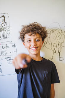 Portrait of happy boy in front of drawing on a whiteboard - DLTSF00211