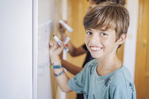 Portrait of smiling boy with a friend drawing on a whiteboard - DLTSF00217