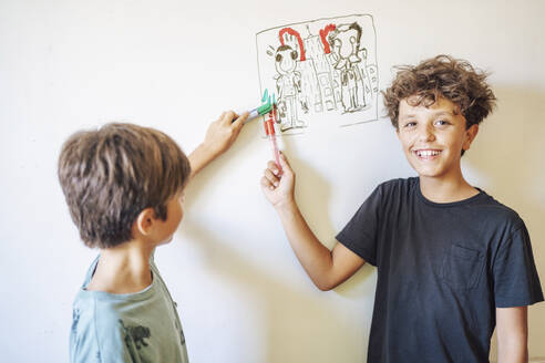 Two boys in front of drawing on a whiteboard - DLTSF00220