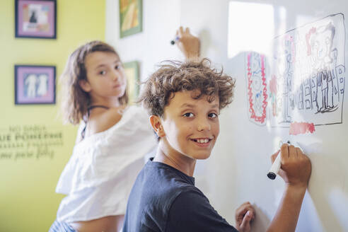 Portrait of smiling boy drawing on a whiteboard with girl in background - DLTSF00223