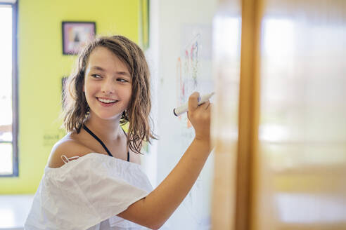 Portrait of smiling girl drawing on a whiteboard - DLTSF00226