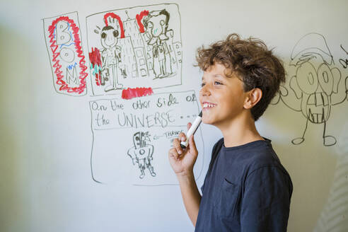 Portrait of happy boy drawing on a whiteboard - DLTSF00229