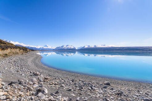 New Zealand, South Island, Clear sky over rocky shore of Lake Pukaki with mountains in background - SMAF01585