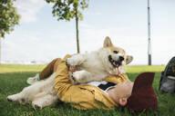 Boy with Welsh Corgi Pembroke in a park - VPIF01588