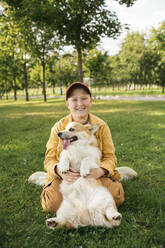 Boy with Welsh Corgi Pembroke in a park - VPIF01591