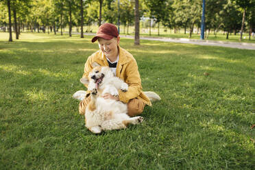Boy with Welsh Corgi Pembroke in a park - VPIF01594