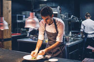 Chef serving food on a plate in the kitchen of a restaurant - CJMF00106