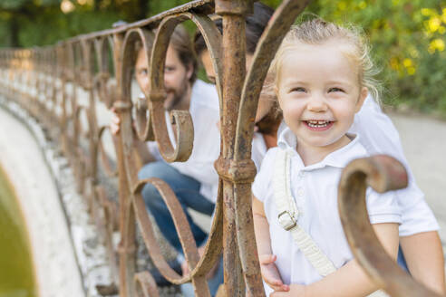 Portrait of happy little girl with parents at a pond - MGIF00761