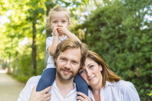 Portait of happy family in a park with father carrying little daughter on his shoulders - MGIF00773