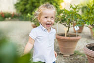 Happy little girl running along flower pots - MGIF00779