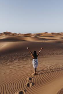 Rear view of young woman walking in the desert, Merzouga, Morocco - DAMF00126