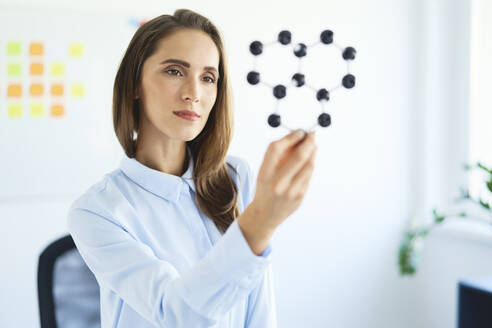 Young female scientist looking at graphene model - BSZF01471