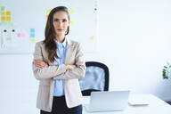 Confident young businesswoman standing in office looking at camera - BSZF01474