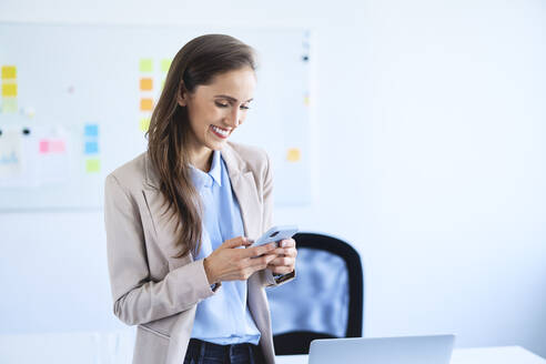 Smiling businesswoman standing in office using smartphone - BSZF01477