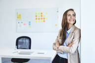Portrait of cheerful businesswoman smiling and looking away in office - BSZF01486