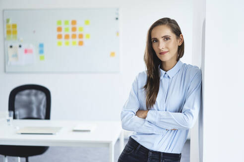 Confident young businesswoman leaning against office wall looking at camera - BSZF01492