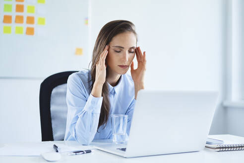 Young businesswoman holding head suffering from headache in office - BSZF01498
