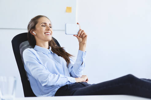 Young businesswoman sitting in office during phone video call - BSZF01501
