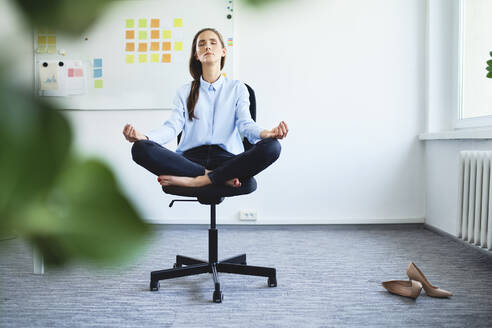 Serene young woman meditating while sitting on office chair - BSZF01504