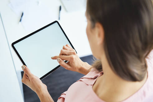Overhead view of woman using tablet in office - BSZF01516