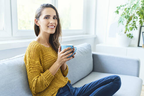 Portrait of young woman drinking coffee sitting on sofa and smiling at camera - BSZF01531