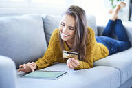 Smiling young woman using credit card and tablet to shop online while lying on sofa - BSZF01540