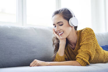 Cheerful young woman lying on sofa and listening to music with headphones - BSZF01543