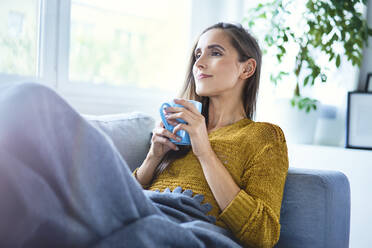 Beautiful young woman enjoying cup of coffee while lying on sofa under blanket - BSZF01546