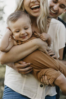 Happy mother hugging her little son outdoors - LHPF01078