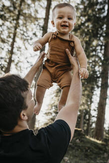 Happy father lifting up little son on a hiking trip in a forest, Schwaegalp, Nesslau, Switzerland - LHPF01084