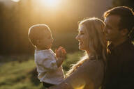 Happy family with little son outdoors at sunset - LHPF01117