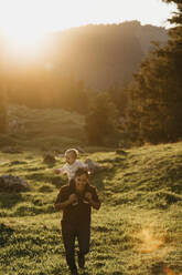 Happy father carrying little son on shoulders on a hiking trip at sunset, Schwaegalp, Nesslau, Switzerland - LHPF01123
