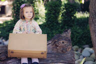 Portrait of little girl sitting on deadwood with leather suitcase - XCF00278