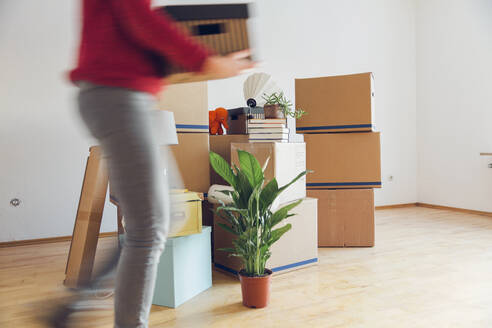 Woman carrying cardboard box in a new home - MAMF00795