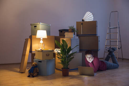 Woman using laptop surrounded by cardboard boxes in a new home - MAMF00801