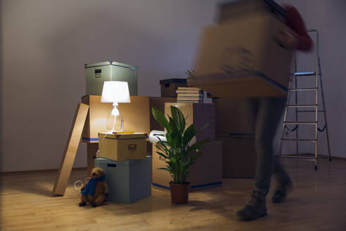 Woman carrying cardboard box in a new home - MAMF00804