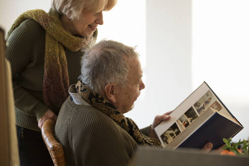 Senior couple looking at photo album surrounded by cardboard boxes in an empty room - MAMF00816