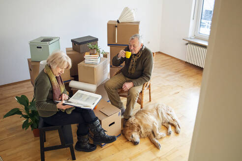 Senior couple having a break surrounded by cardboard boxes in an empty room - MAMF00819