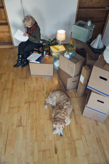 Senior woman looking at papers surrounded by cardboard boxes in an empty room - MAMF00828