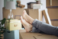 Bare feet of woman relaxing surrounded by cardboard boxes in a new home - MAMF00840