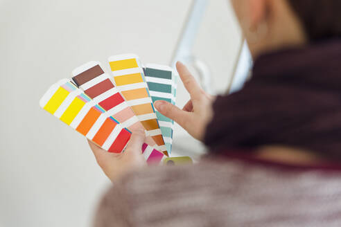 Woman holding colour sample in an empty room with a ladder - MAMF00843