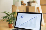 Rising line graph on laptop screen in front of cardboard boxes in a new home - MAMF00846