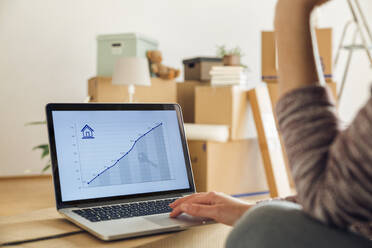 Woman using laptop with rising line graph on the screen in a new home - MAMF00849